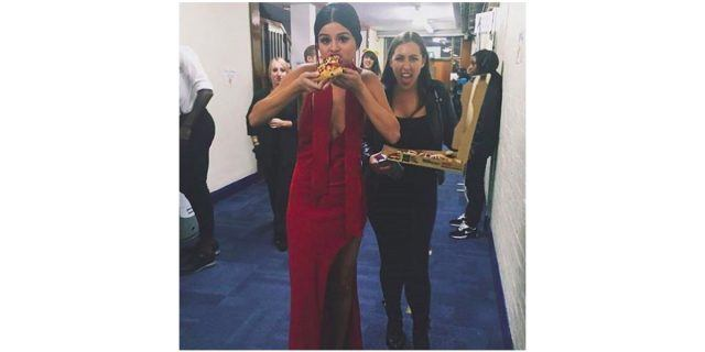 Selena Gomez wears a red evening gown and eats a slice of pizza as her friend, carrying the pizza box, sticks out her tongue.