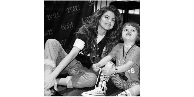 Selena Gomez sits on the floor and poses with a young fan in an image posted to her Instagram account.