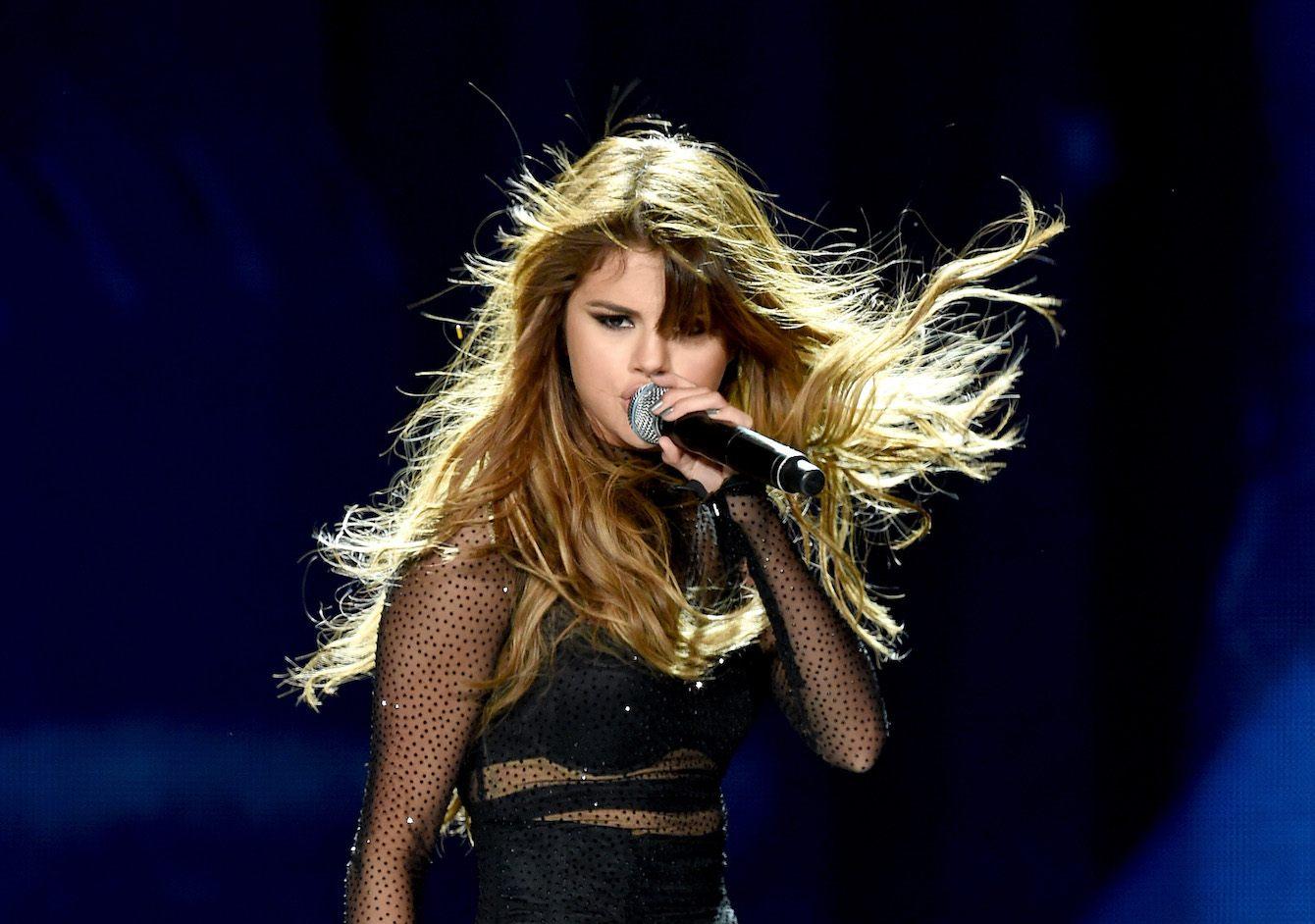 Selena Gomez sings on stage as her hair is blowing in the wind.