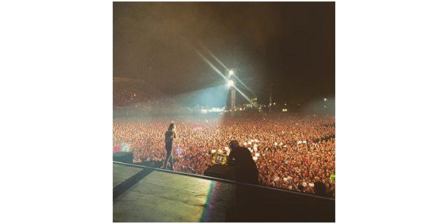 Selena Gomez stands on a stage in front of thousands of fans at night in an image posted to her Instagram account.