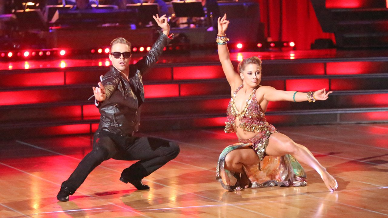 Derek Hough, wearing sunglasses, and Shawn Johnson, crouch low to the ground and strike a pose on 'Dancing With the Stars.'