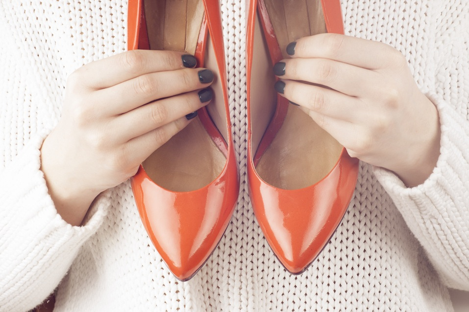 shot of shopping girl holding a red high heel shoe