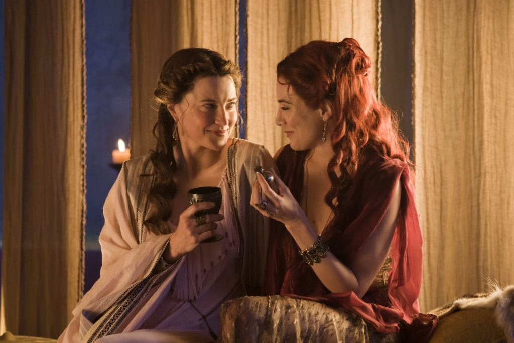 Lucy Lawless and a woman smile together on a bed in Spartacus
