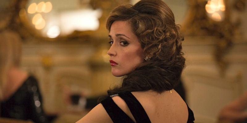 Rose Byrne looks over her shoulder in a black dress in Spy.