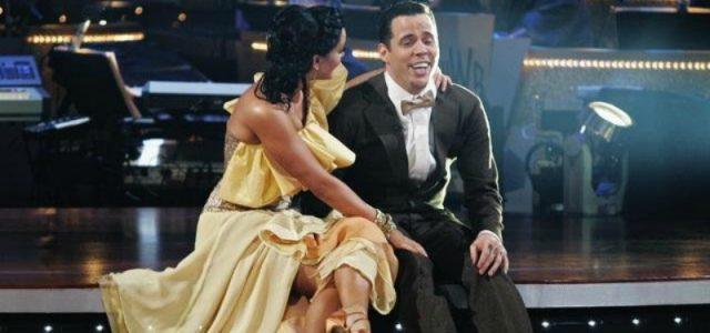 Steve-O is sitting on the steps on stage as Lacey Schwimmer has an arm around him and is looking at him.