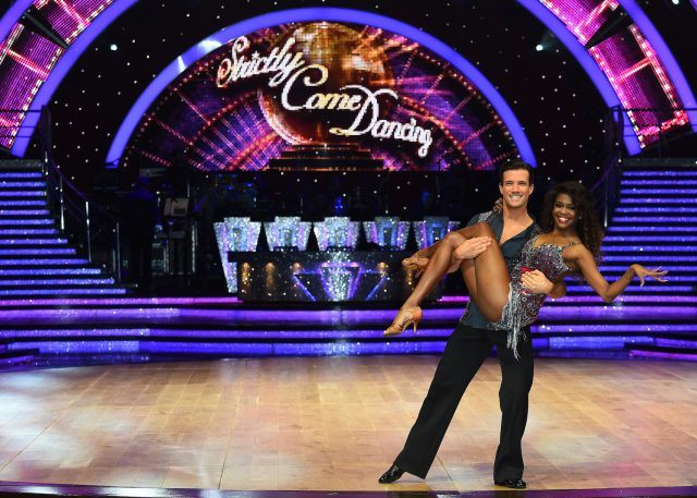 Two contestants pose on the stage for 'Strictly Come Dancing.'