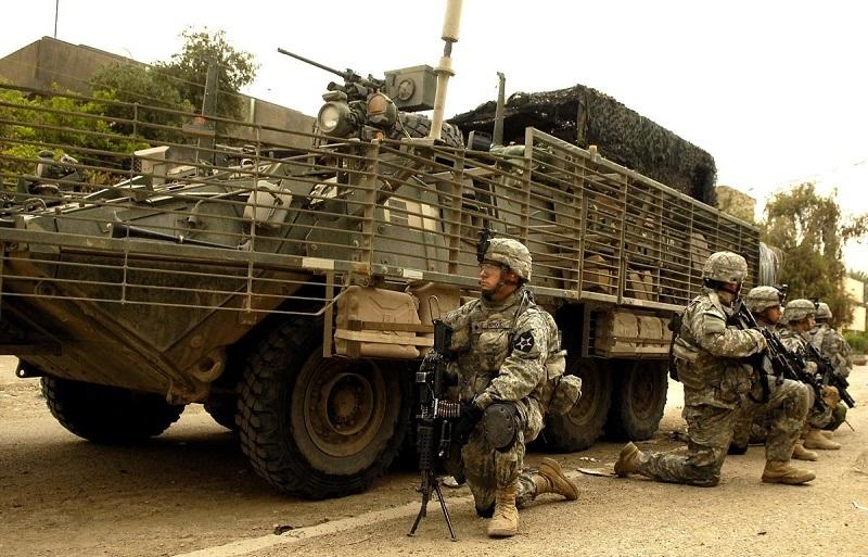 Soldiers kneel alongside a Stryker Combat Vehicle.