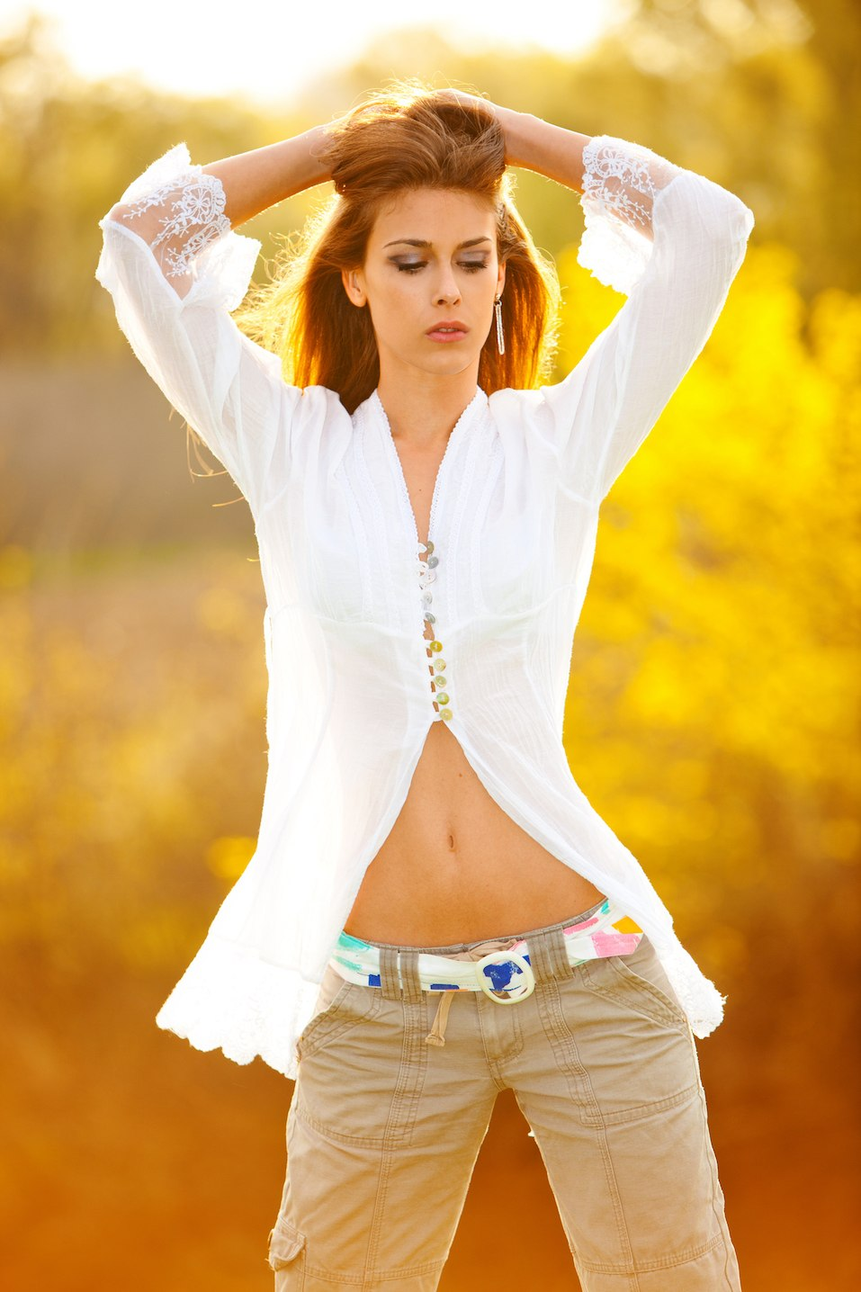 young woman in white shirt on summer meadow at sunset