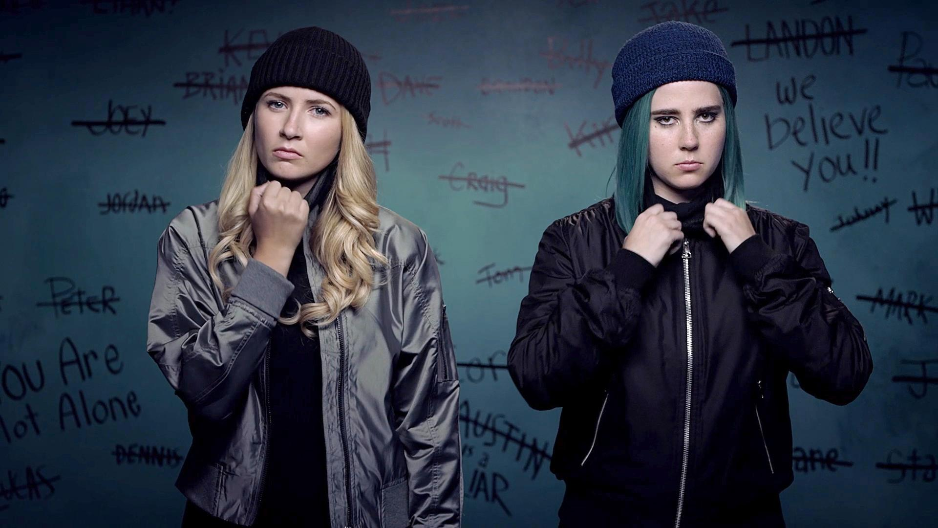 Eliza Bennett and Taylor Dearden stand in front of a wall of graffiti in dark colored caps