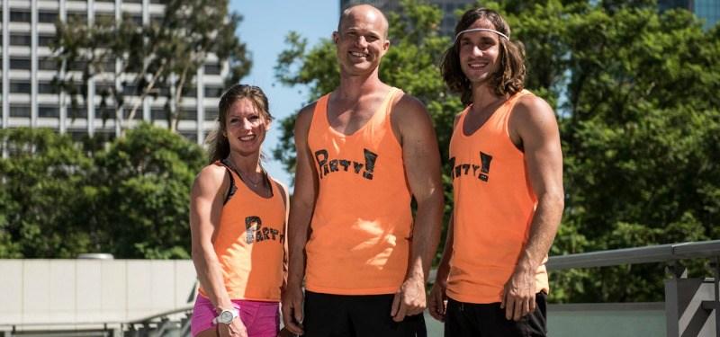 Jennifer Tavernier, Brian Arnold, and Jake Murray pose together in orange uniforms.
