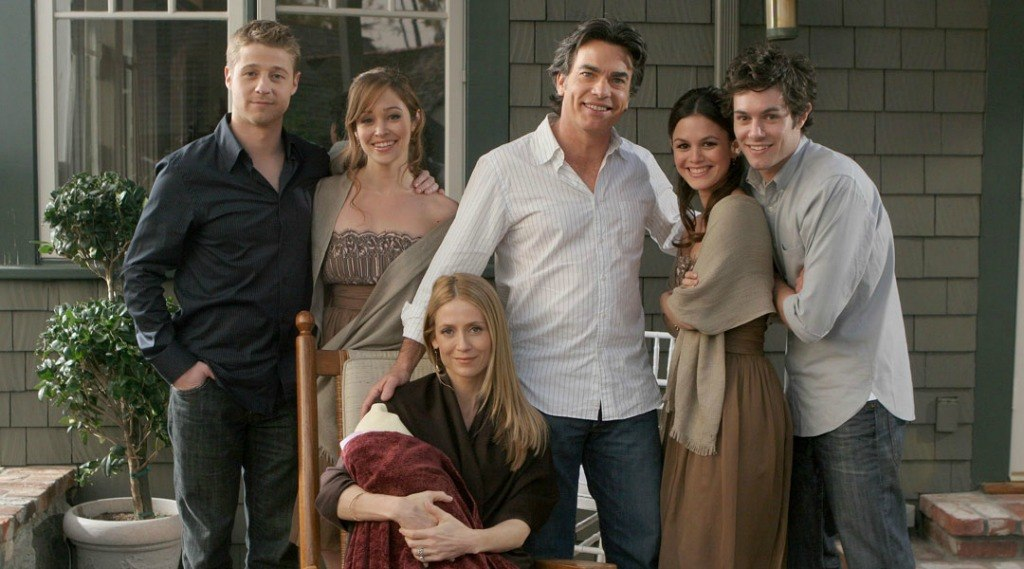 Ben McKenzie as Ryan Atwood, Autumn Reeser as Taylor Townsend, Kelly Rowan as Kirsten Cohen, Peter Gallagher as Sandy Cohen, Rachel Bilson as Summer Roberts, and Adam Brody as Seth Cohen with their arms around each other in front of a house on The O.C.