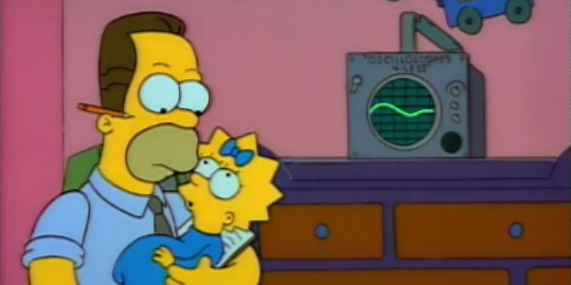 Homer Simpson is holding Lisa and is sitting next to a baby translator device.