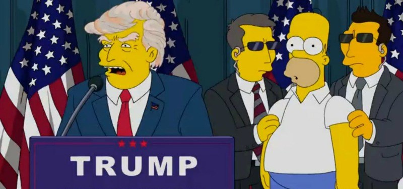 Donald Trump is at a podium while Homer is behind him between two secret service officers.