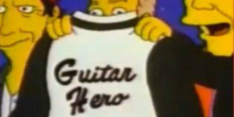 """A man is holding up a jacket that says """"guitar hero"""" in The Simpsons."""