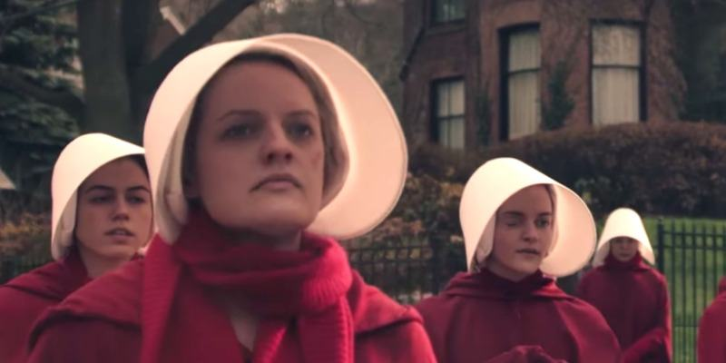 A group of women are wearing red gowns and white bonnets in The Handmaid's Tale.