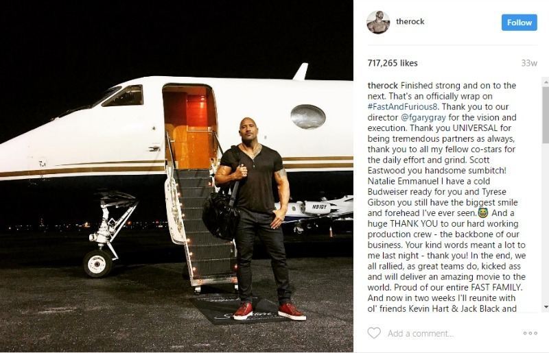 This is a screenshot of a picture of The Rock about to get on a plane.