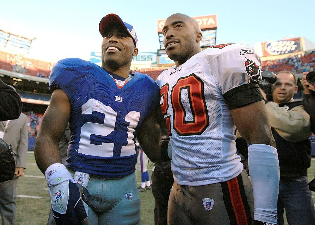 Two football players in uniform standing on a field with their arms around each other