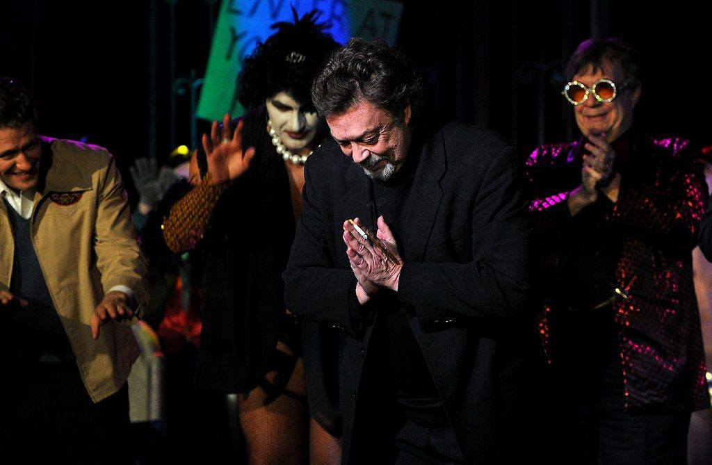 Actor Tim Curry on stage bowing with his hands together and a cigarette in his hand surrounding by performers