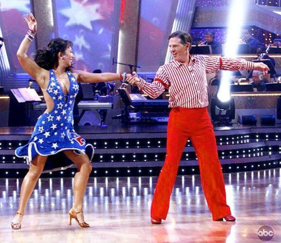 Cheryl Burke wears a blue dress with white stars and Tom Delay wears a red and white striped outfit as they dance on 'Dancing With the Stars.'