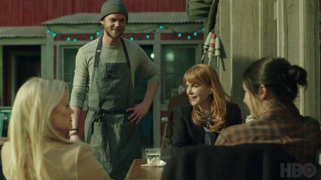 Tom stands with one hand on his hip as he talks to Madeline, Celeste and Jane, all of whom are seated at a table outside his cafe.