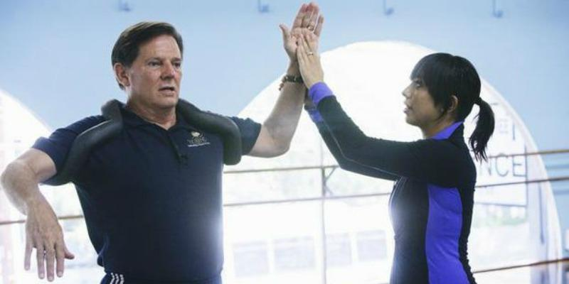 Cheryl Burke is fixing Tom DeLay's form while rehearsing.