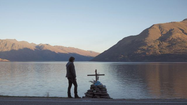 Robin Griffin stands in front of a memorial overlooking a gorgeous lake and mountains in a scene from 'Top of the Lake.'