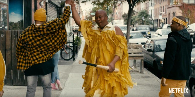 Tituss is dressed up as Beyonce and a bat in one hand and is high fiving someone else with the other.