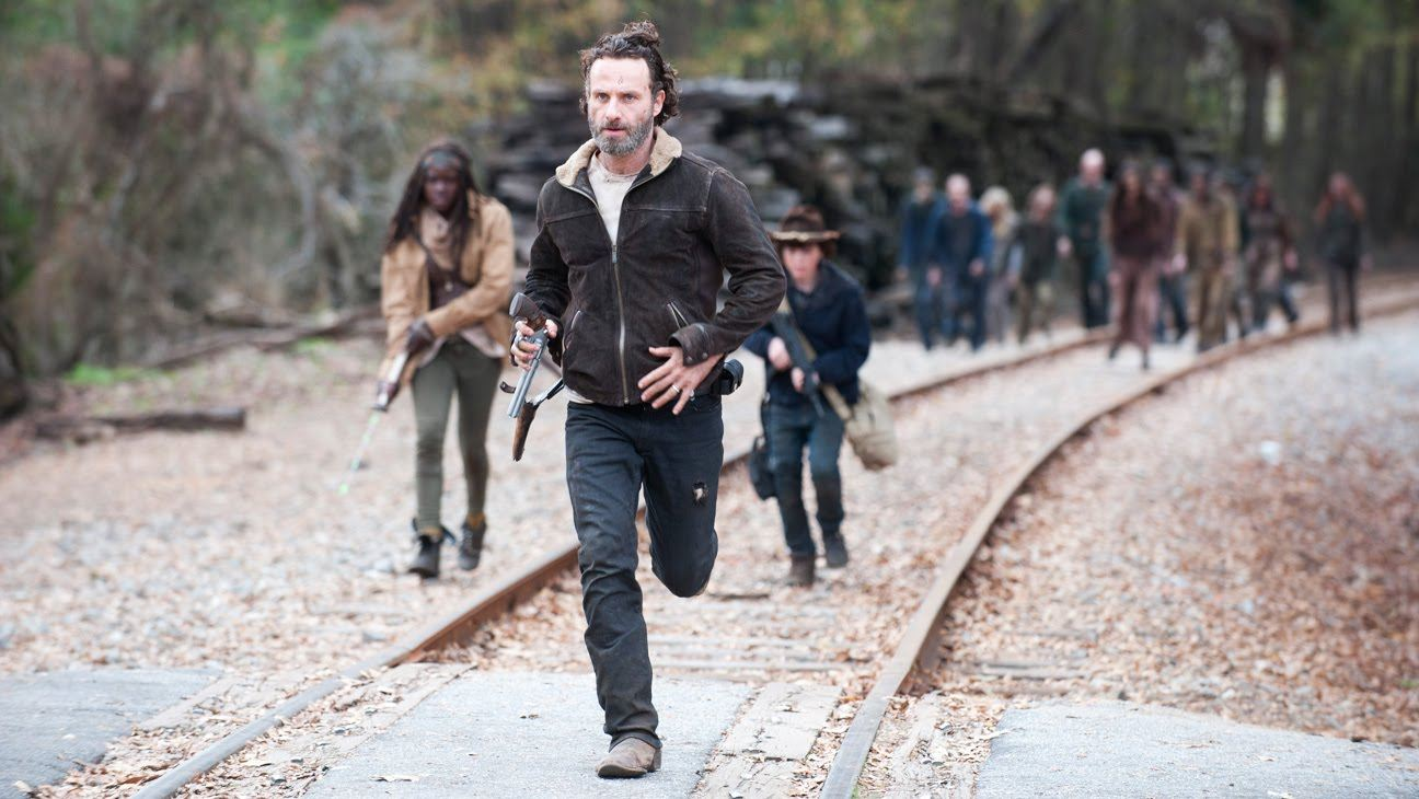 Rick runs on a train track in front of a group