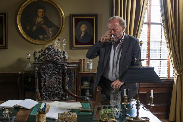 Gregory drinks as he stands in front of his desk in a scene from 'The Walking Dead's seventh season.