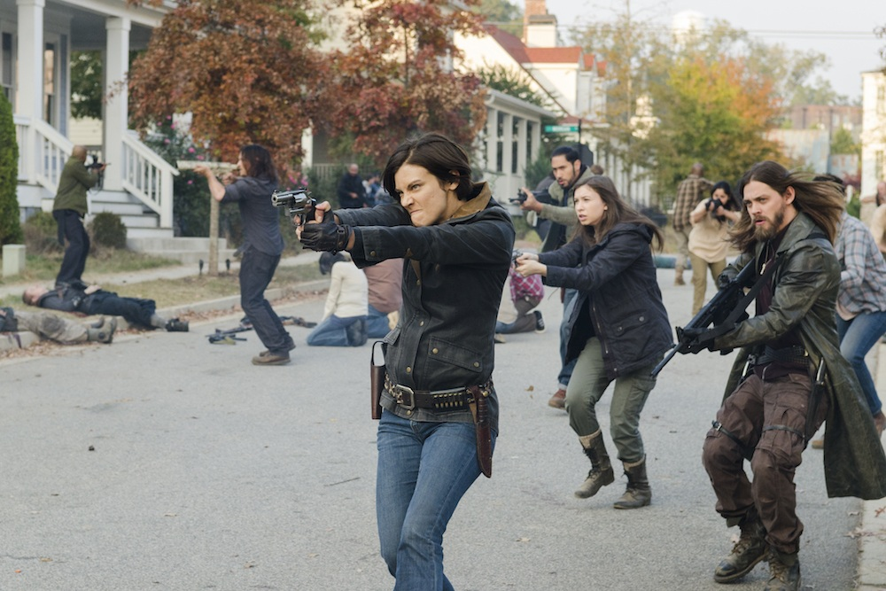 Maggie and other members of Ricks crew hold out guns and prepare to shoot.