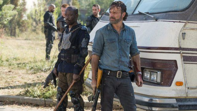 Rick and Morgan both looking off into the distance, holding weapons and standing in front of an RV.