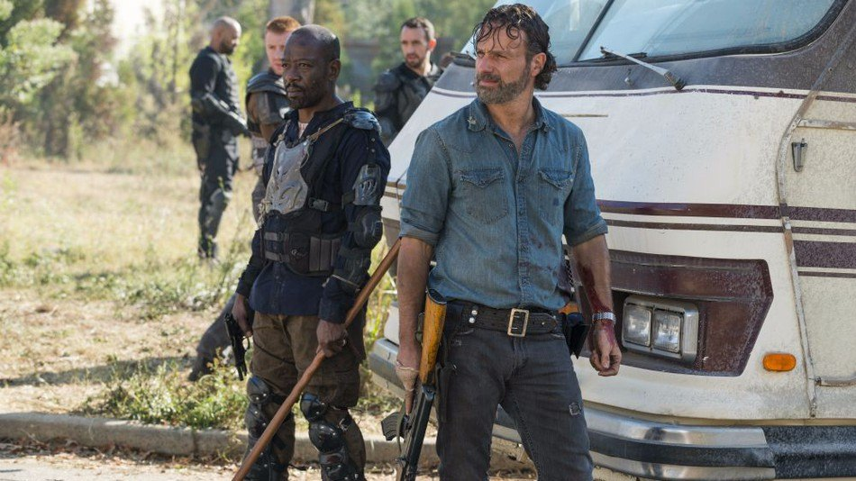 Rick and Morgan both looking off into the distance, holding weapons and standing in front of an RV