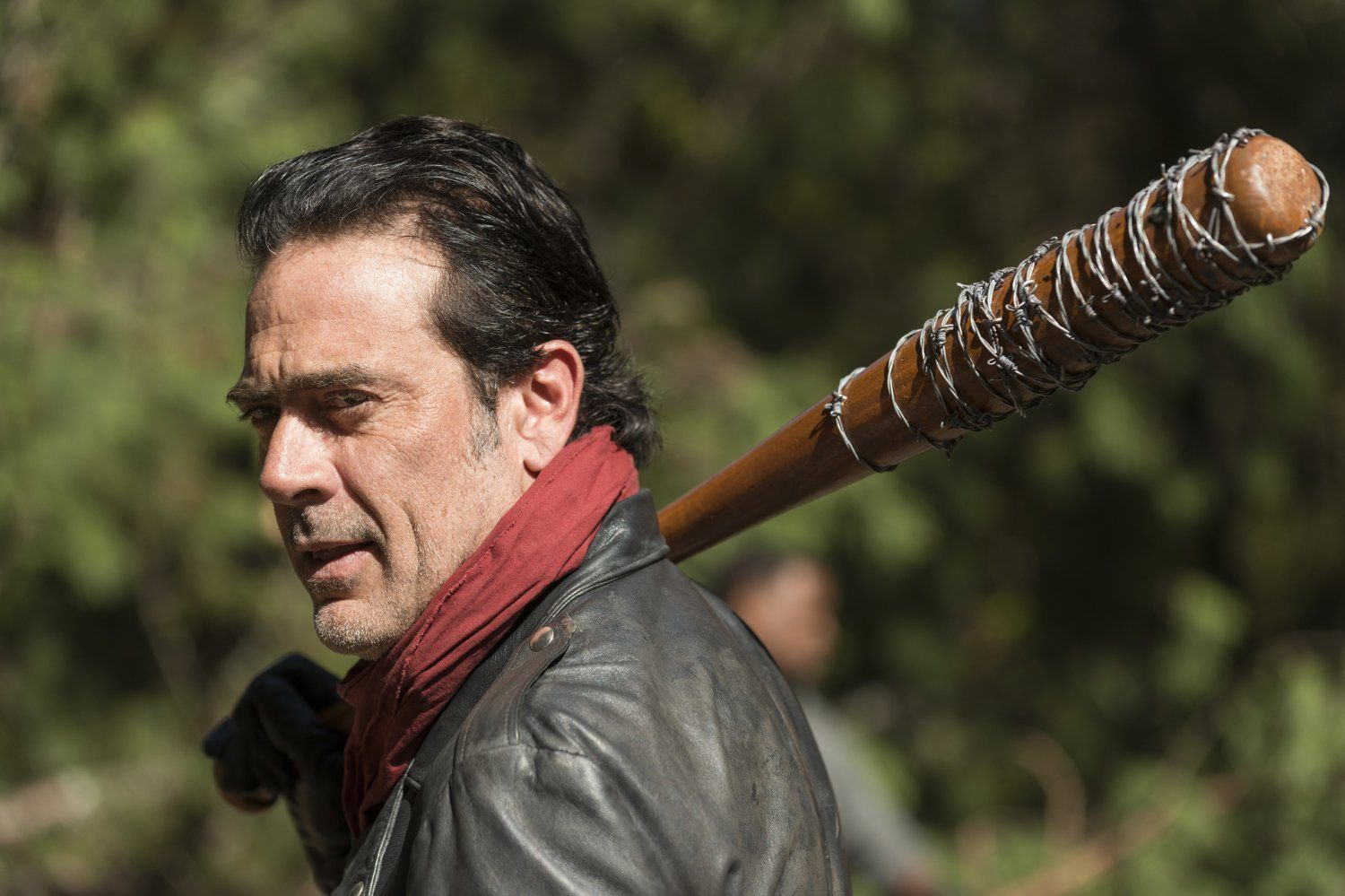 Negan, wearing a red scarf, with a barbed-wire baseball bat on his shoulder