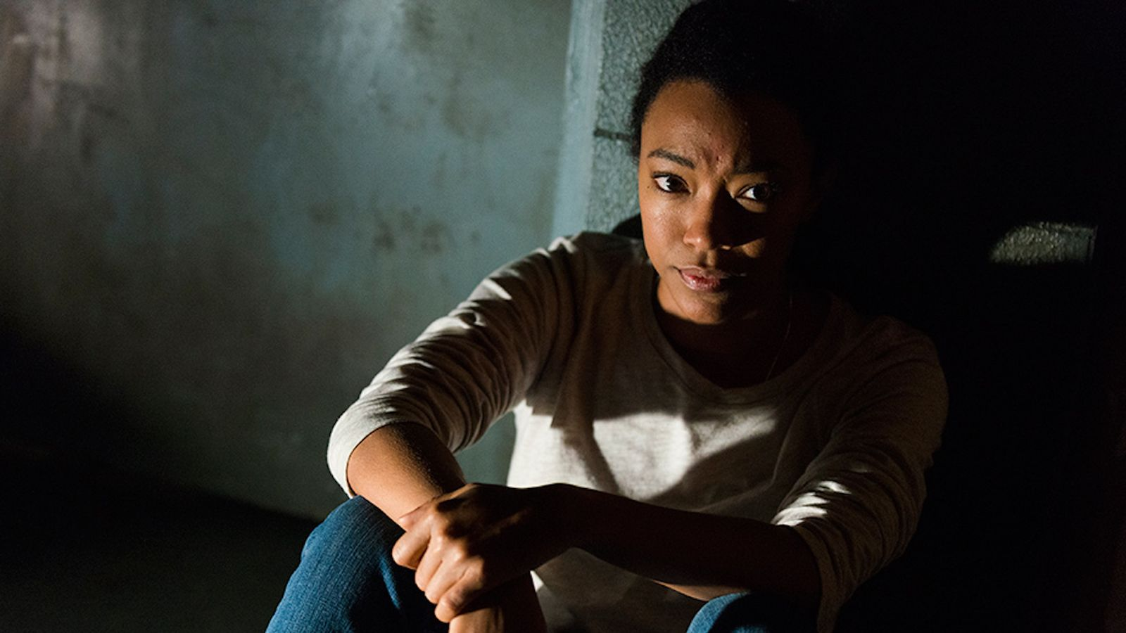 Sonequa Martin-Green as Sasha Williams sitting on the floor in a dark room on The Walking Dead