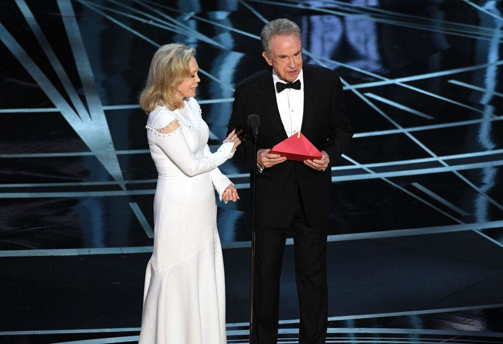 Actors Faye Dunaway and Warren Beatty onstage in formal wear while Beatty holds an envelope and speaks into a microphone at the Oscars