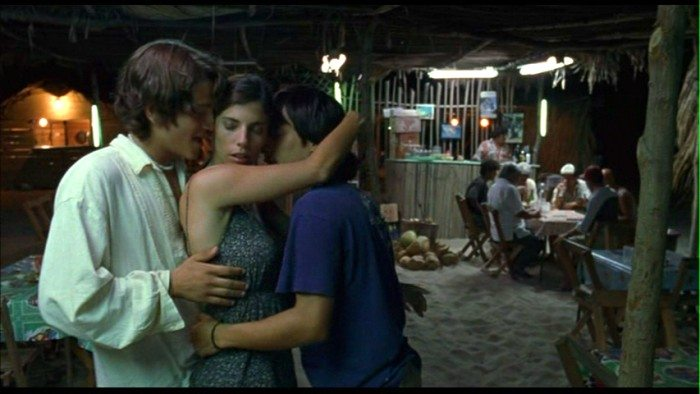 Three young people embrace in a hug, in a dingy, poorly lit room