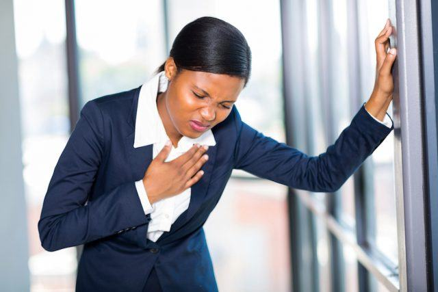 young businesswoman having heart attack or chest pain