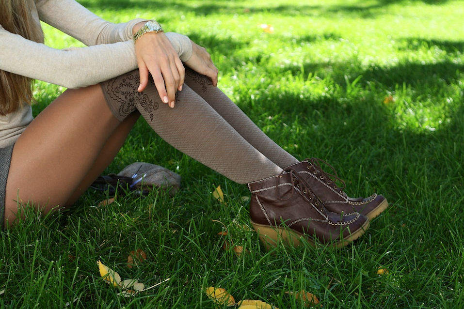 Young beautiful woman slender legs in leather brown boots