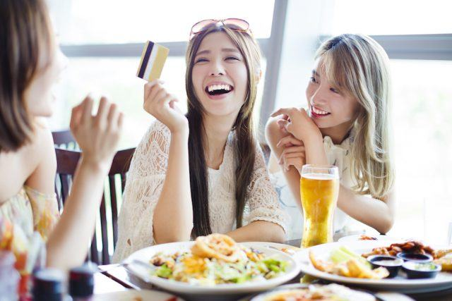 young woman showing credit card at a restaurant