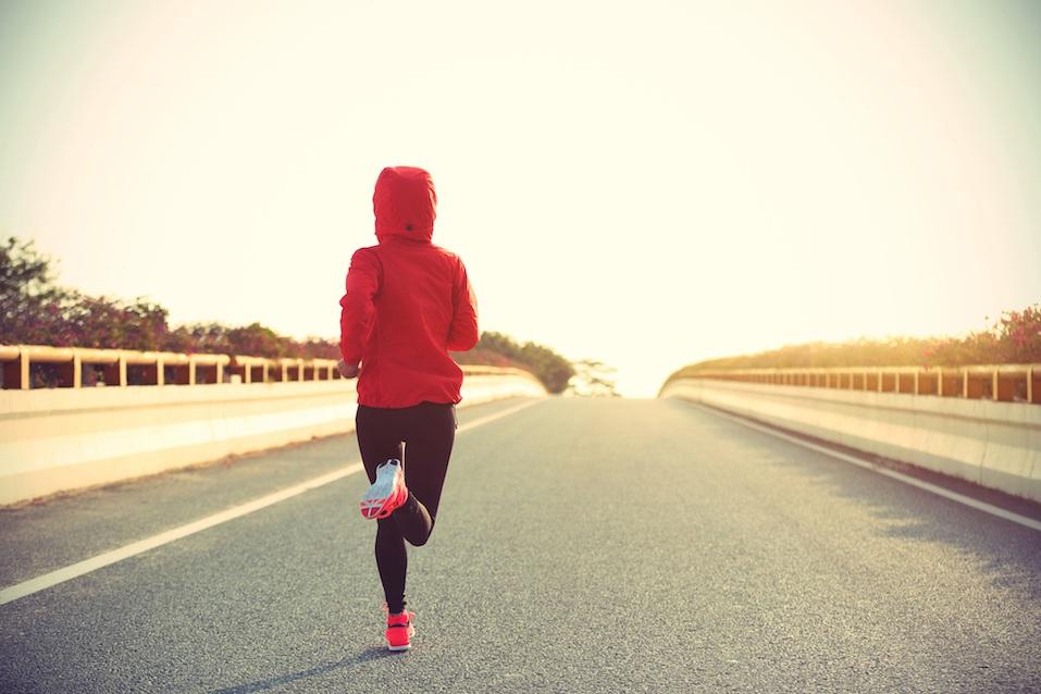 Woman runner running on city road