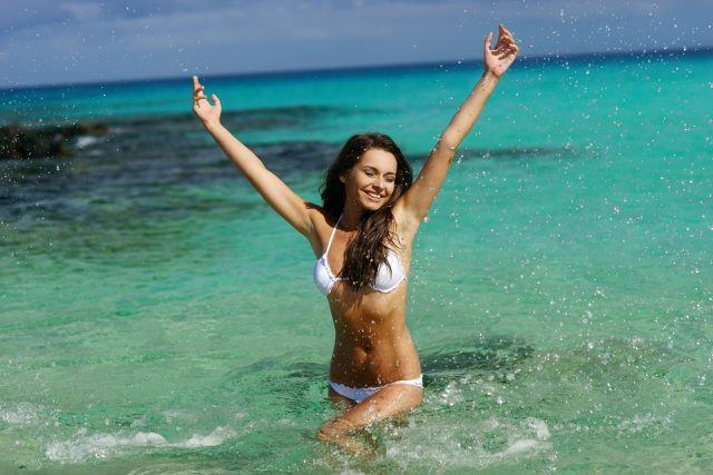 Happy woman playing in blue water