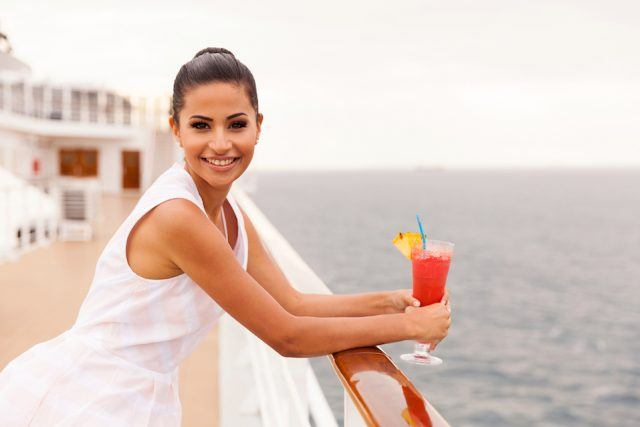 Smiling young woman on a cruise ship holding a cocktail