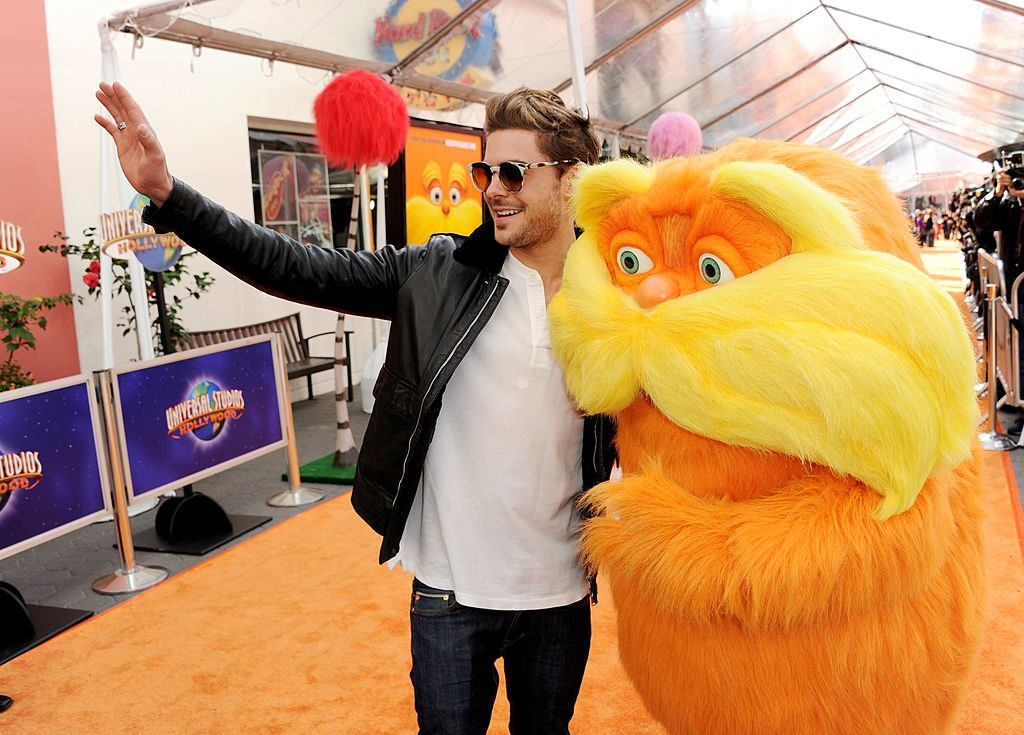Actor Zac Efron waving on the orange carpet at Universal Studios with Lorax character