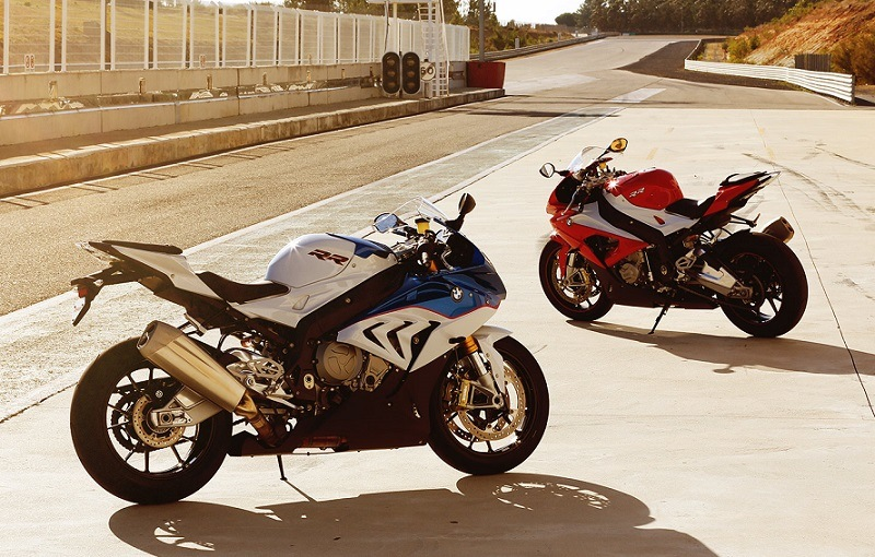 Pair of 2016 BMW S 1000 RR motorcycles parked on the race track at sunset