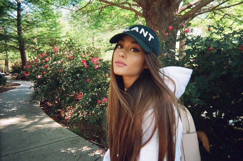 Ariana Grande poses in a baseball cap in front of flowers