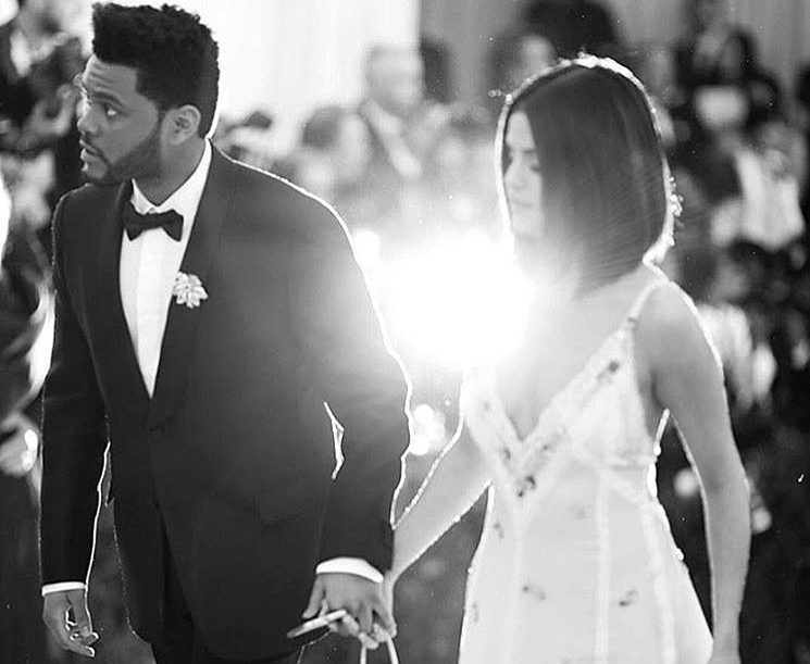 A black-and-white photo of Selena Gomez and The Weeknd walk up the stairs at the 2017 Met Gala
