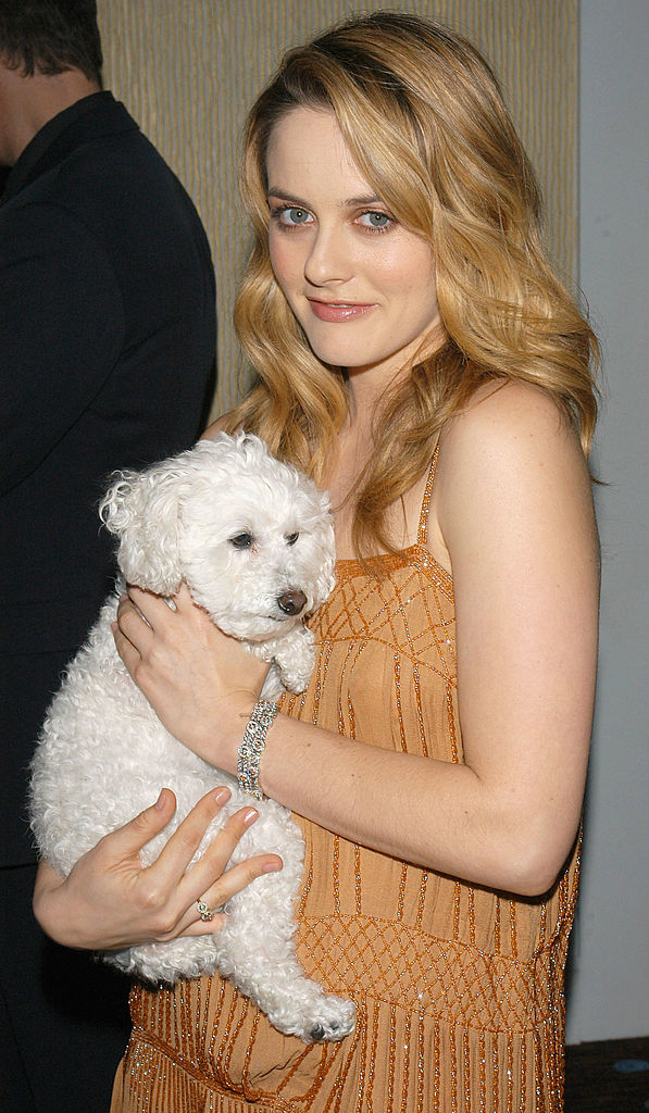 Alicia Silverstone holds a dog.