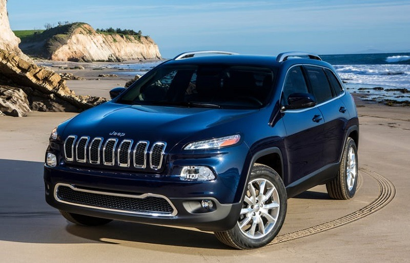 View of 2014 blue Jeep Cherokee parked on a beach