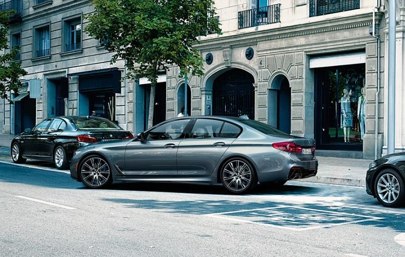 View of 2017 BMW 5 Series sedan parking on a city street