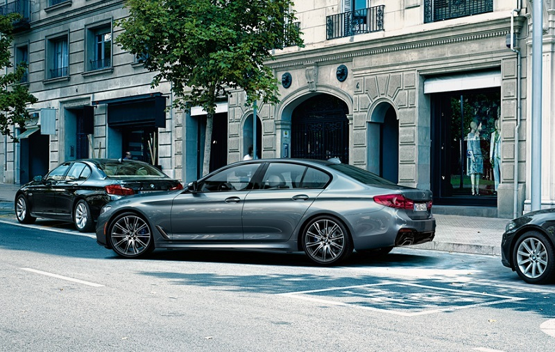 View of 2017 BMW 5 Series sedan parking on a city street